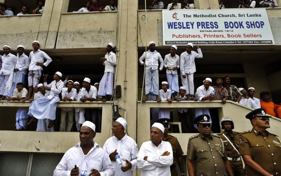 "Sri Lankan Muslims and police officers watch a protest outside the U.S. Embassy in Colombo, Sri Lanka, Monday, Sept. 24, 2012. Thousands of Sri Lankan Muslims protested against the American-produced film ""Innocence of Muslims"" that ridicules Islam's Prophet Muhammad. (AP Photo/Eranga Jayawardena)"