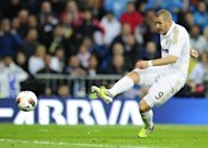 Real Madrid's forward Karim Benzema shoots to score against Sporting Gijon during their Spanish La Liga match at the Santiago Barnabeu stadium in Madrid. Real Madrid came from behind to win 3-1