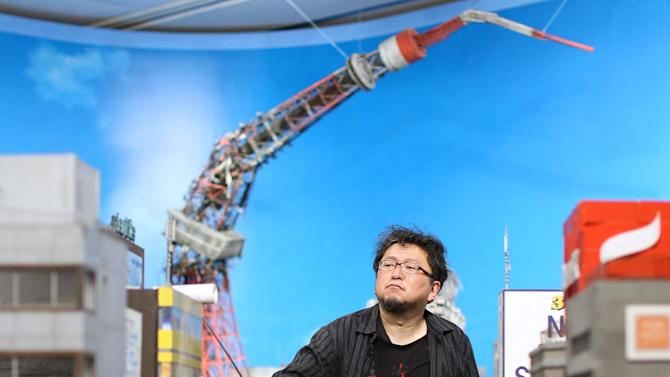 "In this photo taken April 9, 2015 and provided by Yuriko Nakao, director Shinji Higuchi of ""Attack of Titan,"" pretends to clean miniature buildings during a photo opportunity before the opening of ""Museum Director Hideaki Anno's Tokusatsu Special Effects Museum"" at the Contemporary Art Museum, Kumamoto, southern Japan. Higuchi's special-effects techniques were amply demonstrated in ""Attack on Titan,"" a new release received favorably in Japan. (Yuriko Nakao via AP) NO SALES, CREDIT MANDATORY"
