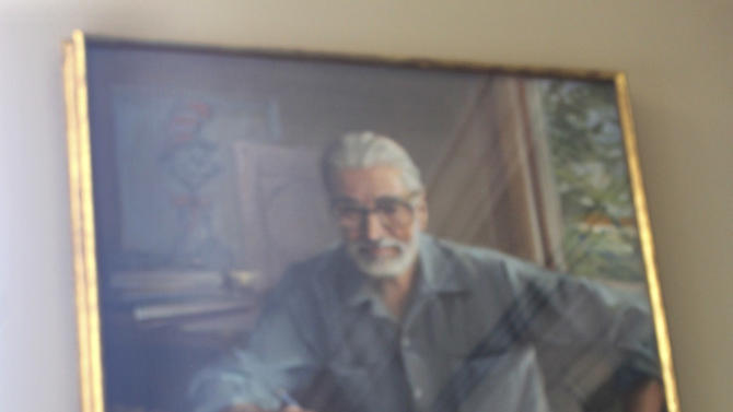 """The newly published book, """"What Pet Should I Get?"""" by Dr. Seuss, is shown in front of a portrait of the author at his alma mater, Dartmouth College  2015 in Hanover, N.H.  Seuss, whose real name was Theodor Geisel, wrote and illustrated more than 40 books before his death in 1991. His wife found the text and illustrations for """"What Pet Should I Get?"""" soon after his death, but the material was set aside and only rediscovered in 2013. (AP Photo/Holly Ramer)"""