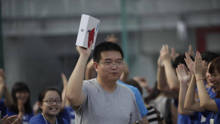 The first customer, Sun Xufei, a 32-year-old software engineer, holds up a box containing Apple's iPad he purchased after an Apple Store started selling its new tablet computers Friday, July 20, 2012 in Shanghai, China. (AP Photo/Eugene Hoshiko)