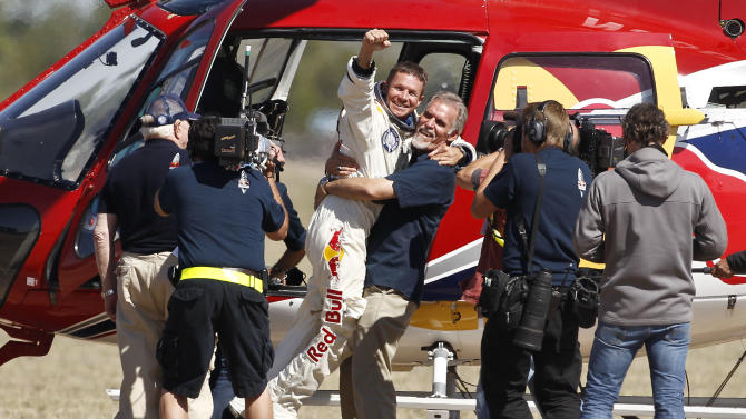 Felix Baumgartner, third from left, of Austria, gets a hug from Mission Control technical project director Art Thompson, as television crews and pool photographers converge on the scene, after Baumgartner successfully jumped from a space capsule lifted by a helium balloon at a height of just over 128,000 feet above the Earth's surface, Sunday, Oct. 14, 2012, in Roswell, N.M.(AP Photo/Ross D. Franklin)