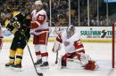 Detroit Red Wings goalie Jimmy Howard makes a save as defenseman Niklas Kronwall (55) and Boston Bruins' Patrice Bergeron look for the rebound during the second period of Game 1 of a first-round NHL playoff hockey series in Boston on Friday, April 18, 2014. (AP Photo/Winslow Townson)