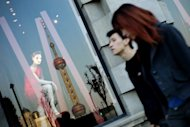 People are seen walking past a luxury shop window showing the reflection of Shanghai's Pearl Tower. Nearly half of China's wealthiest citizens are considering emigrating, with the United States and Canada the most popular destinations, according to a new report from the authors of China's rich list
