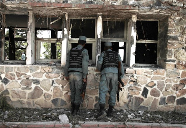 Afghan policemen inspect a damaged room of the Spozhmai hotel on Lake Qurgha where security officials say Taliban insurgents killed nearly two dozen people, most of them civilians, in an attack just n
