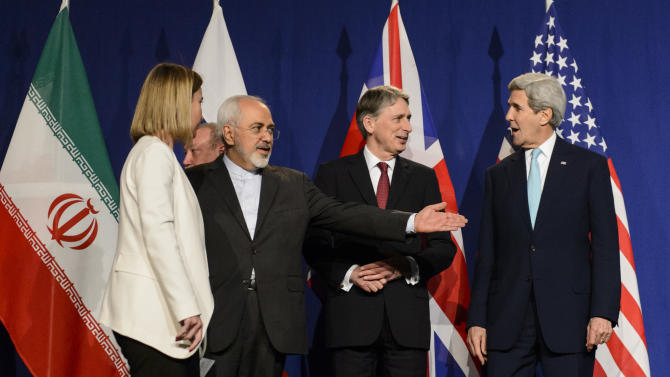 From left, EU High Representative for Foreign Affairs and Security Policy, Federica Mogherini, Iranian Foreign Minister, Mohammad Javad Zarif, British Foreign Secretary, Philip Hammond, and U.S. Secretary of State, John Kerry, line up for a press announcement after the end of a new round of Nuclear Iran Talks in the Learning Center at the Swiss federal Institute of Technology (EPFL), in Lausanne, Switzerland, Thursday, April 2, 2015. (AP Photo/Keystone, Jean-Christophe Bott)