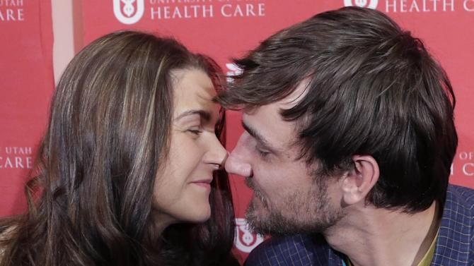 Avalanche survivor, Elisabeth Malloy and skiing partner and initial rescuer Adam Morrey, kiss following their news conference to discuss their avalanche ordeal at the University of Utah Health Care's Burn Center Wednesday, Jan. 16, 2013, in Salt Lake City. Malloy suffered frost bite in her toes and fingers, but emerged otherwise unscathed from Saturday's near-death encounter in the mountains east of Salt Lake City. She survived thanks to her boyfriend, Adam Morrey, avalanche rescue beacons, a skier that wandered by and avalanche rescue teams.  (AP Photo/Rick Bowmer)