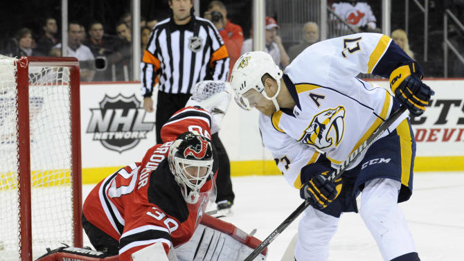 Nashville Predators' Patric Hornqvist, right, of Sweden, skates in on New Jersey Devils goaltender Martin Brodeur during the first period of an NHL hockey game on Sunday, Nov. 10, 2013, in Newark, N.J. (AP Photo/Bill Kostroun)