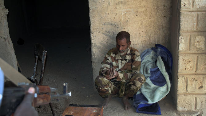 A man suspected of being a Jihadist, arrested by Malian forces in Lere, sits at the police station where he is being held in Timbuktu, Mali, Friday Feb. 1, 2013. French President Francois Hollande is scheduled to visit the fabled city Saturday. (AP Photo/Harouna Traore)