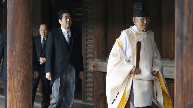 """FILE - In this Dec. 26, 2013, file photo, Japanese Prime Minister Shinzo Abe, second from right, follows a Shinto priest to pay respect for the war dead at Yasukuni Shrine in Tokyo. Abe visited Yasukuni war shrine in a move sure to infuriate China and South Korea. The visit to the shrine, which honors 2.5 million war dead including convicted class A war criminals, appears to be a departure from Abe's """"pragmatic"""" approach to foreign policy, in which he tried to avoid alienating neighboring countries. China and Japan are engaged in a war of words on editorial pages around the world. Beijing has taken aim at a recent visit by Japan's leader to a divisive war shrine, and Tokyo has answered back. (AP Photo/Shizuo Kambayashi, File)"""