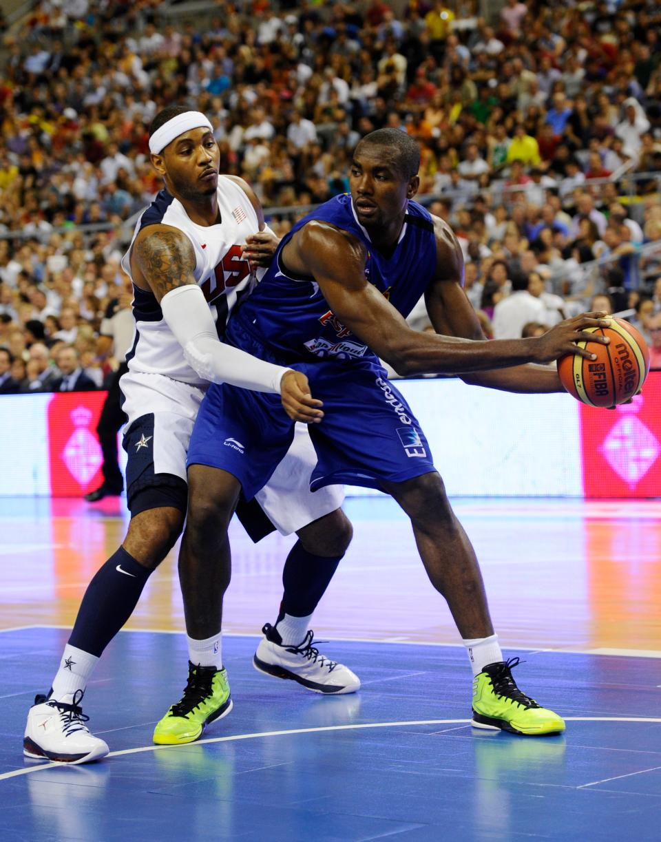 Carmelo Anthony of the US Men's Senior National Team, left, dives for the ball against Serge Ibaka of the Spain Men's Senior National Team during an exhibition match between Spain and the United States Tuesday, July 24, 2012, in Barcelona, Spain, in preparation for the 2012 Summer Olympics. (AP Photo/Manu Fernandez)