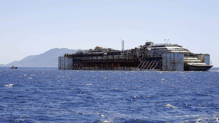 Cruise liner Costa Concordia is dragged by tugboats after leaving Giglio Island