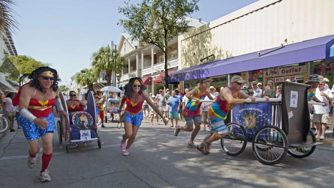 Teams propel decorated beds up Duval Street during the annual Conch Republic Red Ribbon Bed Race in Key West