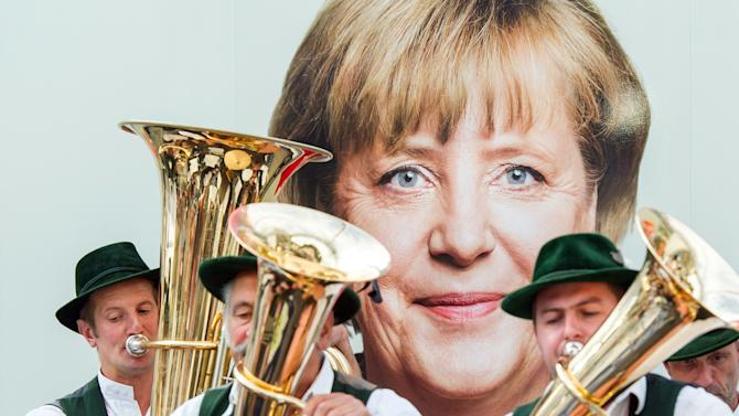 Members of a traditional Bavarian band play in front of an election Poster of German Chancellor Angela Merkel in Miesbach, southern Germany, Wednesday, Sept. 11, 2013. Germany faces general elections on Sept. 22, 2013. (AP Photo/dpa, Marc Mueller)