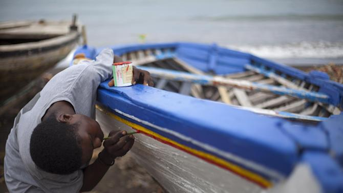 In this May 4, 2013 photo, a man paints a sailboat under construction on the beach of Leogane, Haiti.  The 30-foot-long boats are purchased by smugglers for around $12,000 and then taken to northern Haiti to find passengers. The number of Haitians who don't have enough to eat to maintain a healthy diet has grown from 1.9 million at the end of 2009 to 6.7 million today, said Myrta Kaulard, the country's director for the United Nations' World Food Program.  (AP Photo/Dieu Nalio Chery)