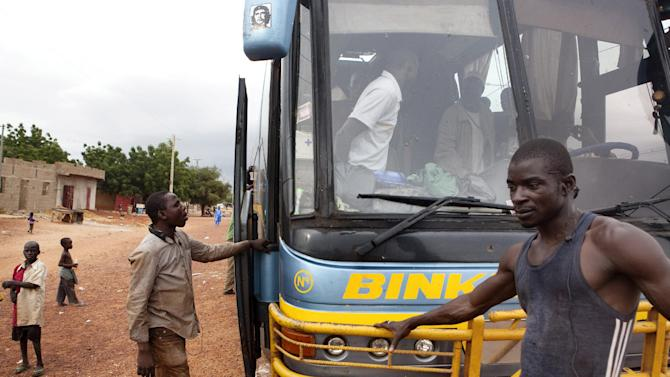 In this Thursday, Sept. 27, 2012 photo, a bus carrying passengers from Gao in Mali's Islamist-controlled north to the capital, Bamako, makes a stop in Mopti, Mali. Passengers began the journey divided by sex, with the women seated behind the men. As soon as the bus crossed the border into government-controlled territory, people switched seats to sit with their families. Ordinary Malians and international experts alike are not sure what will reunite and bring back political stability to a country that until recently had a reputation as one of West Africa's most steady democracies.Representatives of the United Nations, the African Union and regional body ECOWAS are to consider the situation on Oct. 19, 2012 in a meeting in Mali's capital, Bamako. (AP Photo)