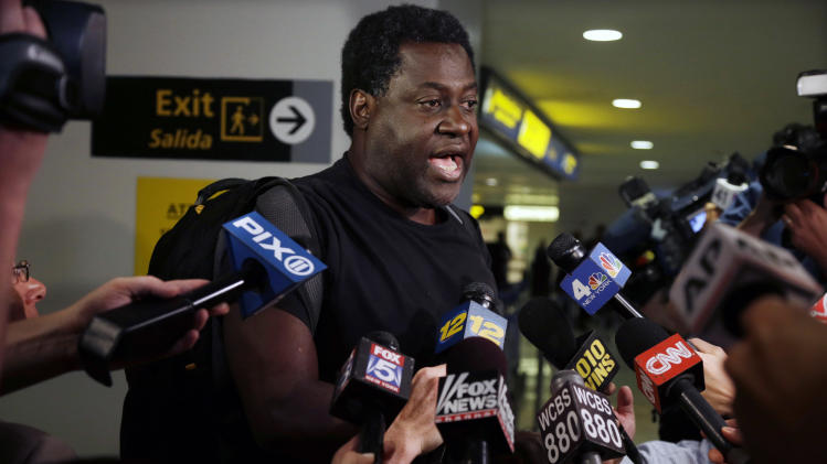 Peter Jones, of Washington, D.C., an airline passenger arriving from Hong Kong answers a question in the international arrivals area at Newark Liberty Airport, Monday, June 17, 2013, in Newark, N.J. , about a fellow passenger who claimed everyone on the flight was poisoned. The plane landed safely at Newark Liberty Airport, and the man was taken off the plane under a heavy police presence. The man stood up during the flight to make the claim but there was no indication that any passengers aboard United Airlines Flight 116 were actually poisoned, an FBI spokesman said. (AP Photo/Mel Evans)