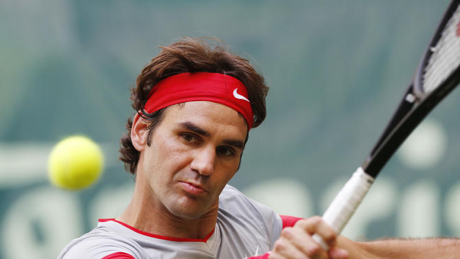 Switzerland's Roger Federer hits a backhand against Japan's Kei Nishikori during their semifinal match of the the Gerry Weber Open tennis tournament in Halle, Germany, Saturday, June 14, 2014. Federer won the match with 6-3 and 7-6. (AP Photo/Michael Probst)