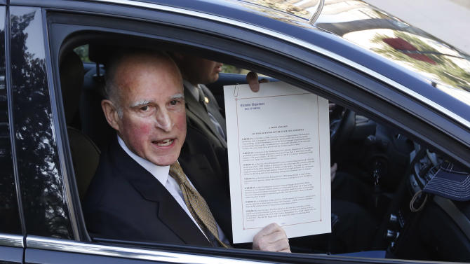 Gov. Jerry Brown displays the proclamation he signed declaring the end to the prison overcrowding emergency, as he leaves the Capitol in Sacramento, Calif., Tuesday, Jan. 8, 2013.   Brown is challenging a federal court order for California to reduce its inmate population and is calling for federal judges to return control of prisons to the state.  Brown's proclamation  will allow the state to phase out the use of private out-of-state prison beds for California inmates starting in July of 2013.(Photo/Rich Pedroncelli)
