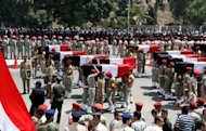 Egyptian military police carry the coffins of 16 soldiers killed in an attack in Sinai during their funeral in Cairo on August 7. Egypt's military killed 20 militants in a helicopter strike in Sinai on Wednesday, state television reported, days after 16 of its soldiers were killed in an attack attributed to Islamic extremists