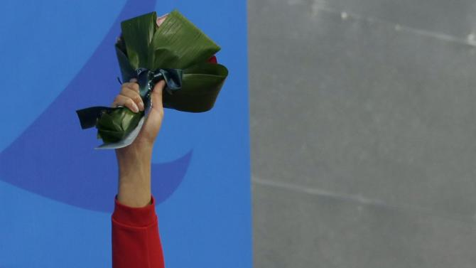 Bronze medalist Schooling of Singapore raises his bouquet at an award ceremony after the men's 200m butterfly final swimming competition during the 17th Asian Games in Incheon