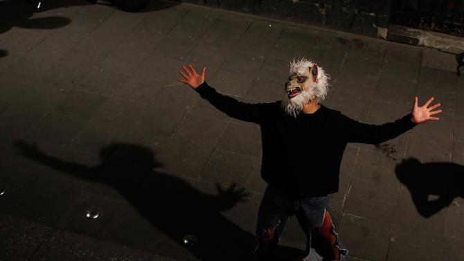 Man wearing a werewolf mask sings in an alley in downtown Mexico City