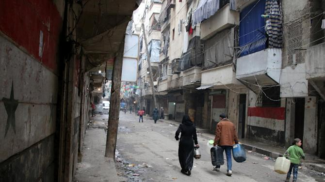 Civilians walk with containers for fuel and water in Aleppo, Syria, Thursday, Feb. 11, 2016.  The fighting around Syria's largest city of Aleppo has brought government forces closer to the Turkish border than at any point in recent years, routing rebels from key areas and creating a humanitarian disaster as tens of thousands of people flee. (Alexander Kots/Komsomolskaya Pravda via AP)
