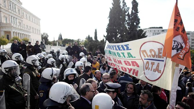 "Greek riot police prevent protesting municipal employees who pushed into the grounds of Parliament from advancing any further, during a protest in Athens on Wednesday, Dec. 12, 2012. The banner reads: ""No to sackings, the measures will not be enforced."" Municipal employees are angry at government plans to include them on a list of state employees up for forced redundancy under the country's austerity program. (AP Photo/Petros Giannakouris)"