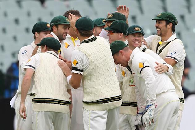 The Australians congratulate teammate Nathan Lyon, left, for catching England's Stuart Broad during the fifth day of the second Ashes cricket test match between England and Australia, in Adelaide,