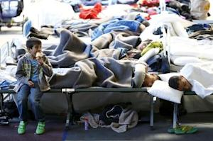 Migrants rest at an temporary shelter in a sports hall …