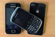 A Samsung mobile phone, a Blackberry phone and an Apple iPhone 4. Using smartphones or tablets as digital &quot;wallets&quot; will be common within a decade, largely replacing cash and credit cards, according to a Pew Research survey released on Tuesday