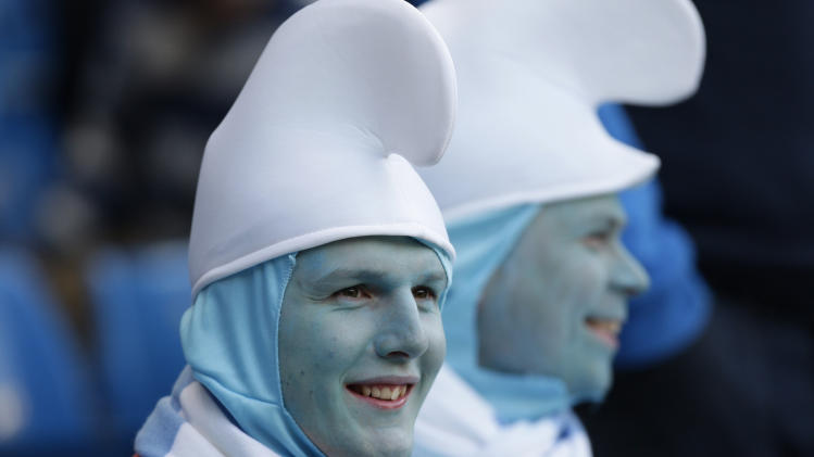 Manchester City supporters in fancy dress take their seats before their team's English Premier League soccer match against Manchester United at The Etihad Stadium, Manchester, England, Monday, April 30, 2012. (AP Photo/Jon Super)