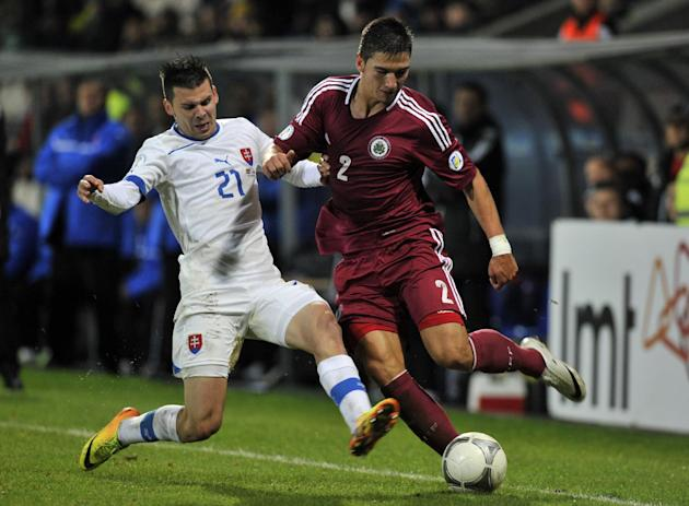 Latvia's Vitalijs Maksimenko, right, vies for the ball with Slovakia's Michal Duris during a World Cup 2014 Group G qualification match in Riga, Latvia, on Tuesday. October 15, 2013