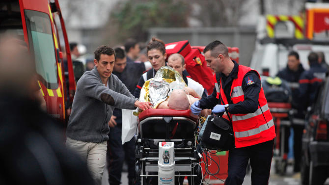 FILE - In this Wednesday Jan. 7, 2015, file photo, an injured person is transported to an ambulance after a shooting at the French satirical newspaper Charlie Hebdo's office in Paris, France. Though it is impossible to gauge in any tangible way the effect the deadly attack on a Paris newspaper will have on recruitment by extremist groups - and there is no evidence so far that it is mobilizing large numbers of would-be jihadis - experts believe the perceived professionalism of the brothers' assault and their subsequent showdown with police could rally more supporters to militant ranks. (AP Photo/Thibault Camus)
