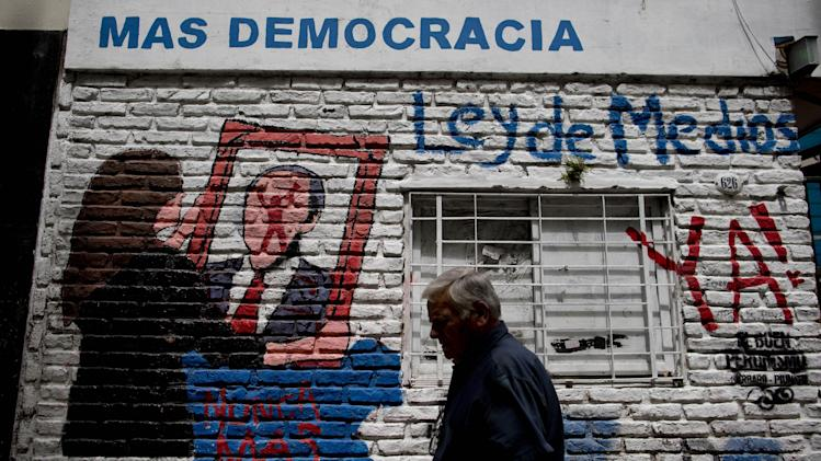 "A man walks by a mural depicting Argentina's President Cristina Fernandez, holding a frame over the image of a man with a Clarin newspaper logo on the face, with a message that reads in Spanish; ""More democracy, Media Law now!,"" in Buenos Aires , Argentina, Tuesday, Oct. 29, 2013. Argentina's Supreme Court approved the country's four-year-old broadcast media law on Tuesday, deciding that it's constitutional to force private news media monopolies to break themselves apart if they exceed government-imposed audience limits. The historic ruling is a huge victory for Fernandez and a bitter defeat for Grupo Clarin, which has been a leading voice against her administration. (AP Photo/Natacha Pisarenko)"