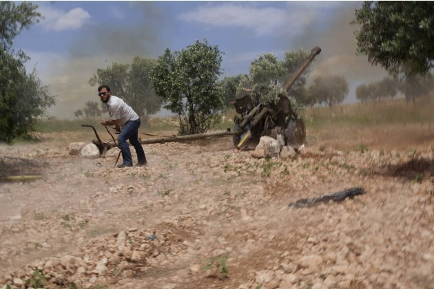 A Free Syrian Army fighter launches a weapon towards Syrian Regime troops in Aleppo's countryside