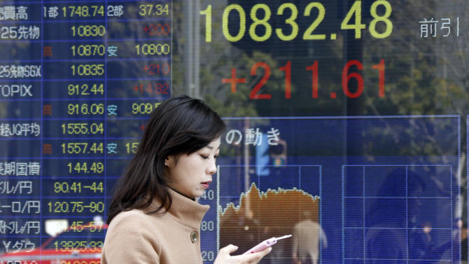 A woman walks by an electronic stock board of a securities firm in Tokyo, Friday, Jan. 25, 2013.  Japan's benchmark stock index jumped about 2 percent Friday after the country's currency continued to slide against the dollar. (AP Photo/Koji Sasahara)