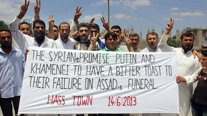 "In this citizen journalism image provided by Edlib News Network, ENN, which has been authenticated based on its contents and other AP reporting, anti-Syrian regime protesters hold a banner and flash the victory sign during a demonstration in Hass town, Idlib province, northern Syria, Friday, June 14, 2013. The Syrian government on Friday dismissed U.S. charges that it used chemical weapons as ""full of lies,"" accusing President Barack Obama of resorting to fabrications to justify his decision to arm Syrian rebels. The commander of the main rebel umbrella group welcomed the U.S. move. (AP Photo/Edlib News Network ENN)"