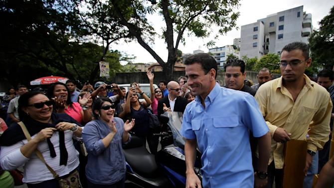 Miranda's  Gov. Henrique Capriles, front, second from right, smiles upon his arrival to a polling station in Caracas, Venezuela, Sunday, Dec. 16, 2012. Venezuelans are choosing governors and state lawmakers  in elections that have become a key test of whether President Hugo Chavez's movement can endure if the socialist leader leaves the political stage. (AP Photo/Fernando Llano)