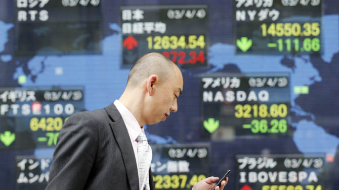 """A man checks his mobile phone as he walks by an electronic stock board of a securities firm in Tokyo showing Japan's benchmark Nikkei 225 stock index, center top, that gained 272.34 points to 12,634.54 Thursday, April 4, 2013. Earlier in the day the Bank of Japan announced a policy overhaul intended to double the money supply and achieve a 2 percent inflation target at the """"earliest possible time, with a time horizon of about two years."""" Financial markets reacted with relief. (AP Photo/Koji Sasahara)"""