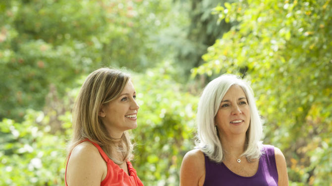 Emily Jordan, left, and her pregnant mother Cindy Reutzel relax at Jordan's home on Sunday, Aug. 19, 2012 in Naperville, Ill. After Jordan underwent a radical hysterectomy, she and her husband took up an offer from Reutzel to act as their surrogate. (AP Photo/Sitthixay Ditthavong)