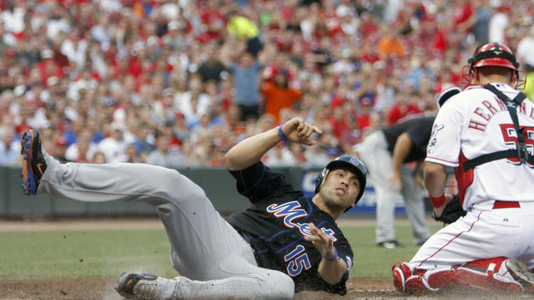 New York Mets' Carlos Beltran, left, slides safely into home plate past Cincinnati Reds catcher Ramon Hernandez, right, after a Jason Bay sacrifice fly during the third inning of a baseball game, Tuesday, July 26, 2011, in Cincinnati. (AP Photo/David Kohl)