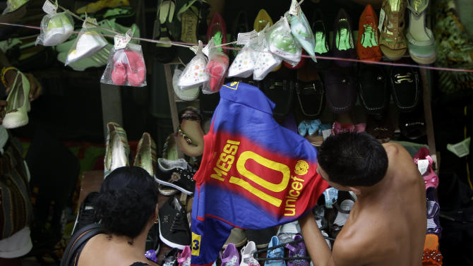 A shopper looks at a copy of a FC Barcelona soccer team shirt with the name of player Lionel Messi at an outdoor market where the government allows licensed vendors to sell their goods in downtown Havana, Cuba, Friday, Aug. 31, 2012. A jump in import taxes on Monday, Sept. 3 threatens to make life tougher for some of Cuba's new entrepreneurs who the government has been trying to encourage as it cuts a bloated workforce in the socialist economy. In Cuba, the average monthly wage is about $20. (AP Photo/Franklin Reyes)
