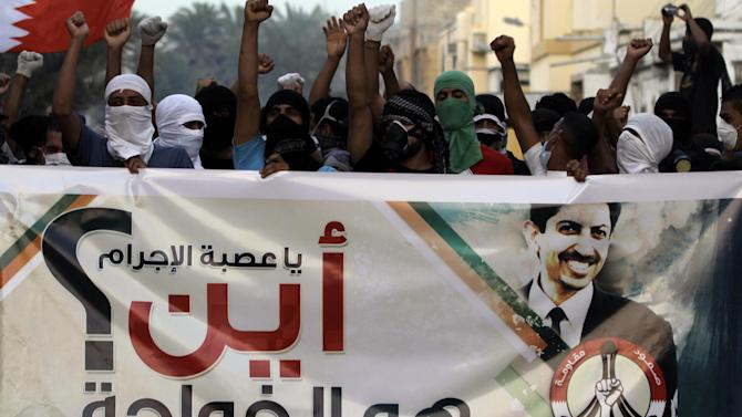 """Bahraini anti-government protesters wave national flags and chant in support of jailed opposition rights activist Abdulhadi al-Khawaja on Saturday, April 28, 2012, in Abu Saiba, Bahrain. Al-Khawaja, pictured on the banner reading """"You criminals, where is al-Khawaja?""""has been on a hunger strike for 80 days, but his family and lawyer have raised concerns saying they have not been allowed contact with him for several days. (AP Photo/Hasan Jamali)"""