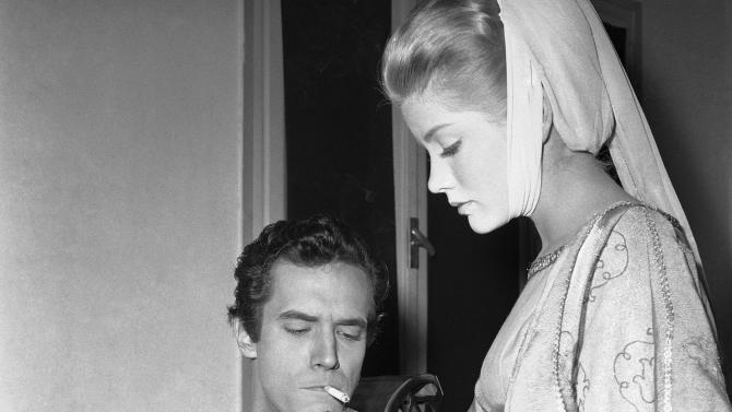 "FILE - In this Dec. 19, 1960 file photo, actress Dolores Hart lights a cigarette for actor Bradford Dillman, in a break of the shooting of the movie, ""Saint Francis of Assisi,"" in Rome. Dillman had the starring role of Saint Francis, while Hart played the part of Saint Clare, the nun who founded the order of St. Clare. Hart, whose luminous blue eyes entranced Elvis Presley in his first on-screen movie kiss, is now a cloistered nun and praying for a Christmas miracle. She walked away from Hollywood stardom in 1963 to become a nun in rural Bethlehem, Conn. Now she finds herself back in the spotlight, but this time it's all about serving the King of Kings, not smooching the King of Rock and Roll. The former brass factory that houses Mother Dolores and about 40 other nuns cloistered at the Abbey of Regina Laudis in Bethlehem, Conn., needs millions of dollars in renovations to meet fire and safety codes, add an elevator and make handicap accessibility upgrades. (AP Photo/CR, File)"