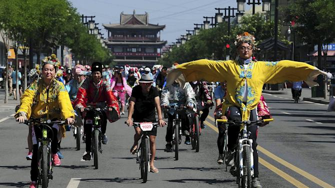 A man in traditional Chinese emperor costume gestures as he and other participants ride their bicycles along a street, during a cycling event in Datong
