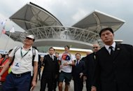 "Roger Federer (C) is flanked by security guards as he makes his way to the practice courts ahead of the Shanghai Masters tournament. A blogger in China who made a death threat against Federer said he had apologised but remained at large after vowing to ""assassinate"" the world number one, according to an Internet posting"