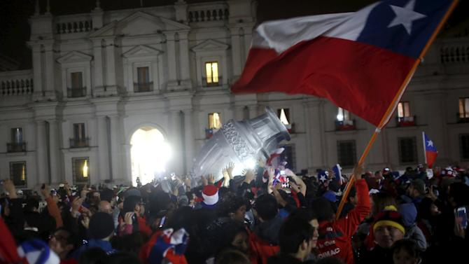 Fans celebrate with a Chilean national flag and giant Copa America trophy outside the La Moneda presidential palace after Chile defeated Argentina to win the Copa America final soccer match in Santiago