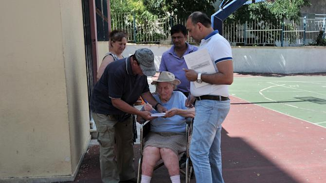 Referendum officials and relatives help an elderly woman _ who was unable to walk up a flight of stairs to a polling station _ cast her vote in Athens, Sunday, July 5, 2015. Greeks were voting Sunday in a bailout referendum that will decide the country's future, with opinion polls showing people evenly split on whether to accept creditors' proposals for more austerity in exchange for rescue loans or defiantly reject the deal. (AP Photo/Angelos Christofilopoulos)