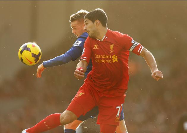Liverpool's Suarez challenges Cardiff City's Gunnarsson during their English Premier League soccer match at Anfield in Liverpool